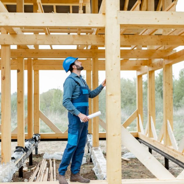 Builder on the wooden house structure on the construction site