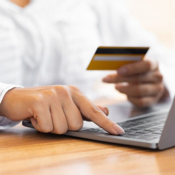 Woman using pc and credit card at home